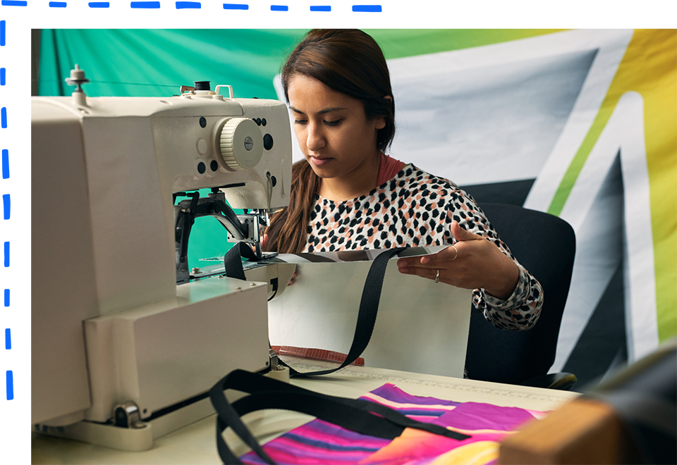 MHW employee using a sewing machine to make a vinyl bag